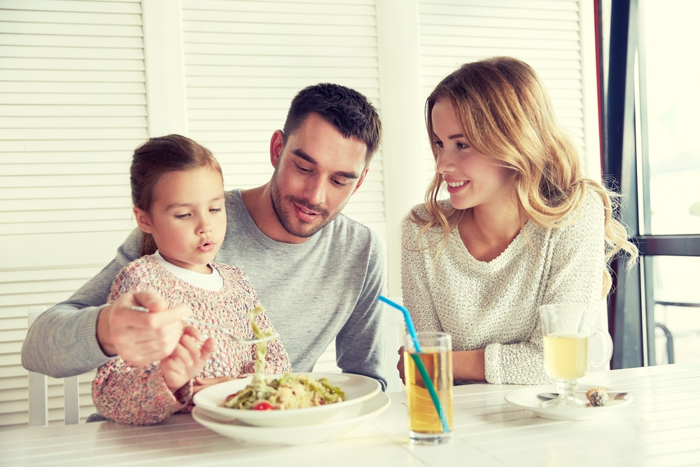 Happy mother, father and little girl eating pasta at the table, with two cups of juice on it.