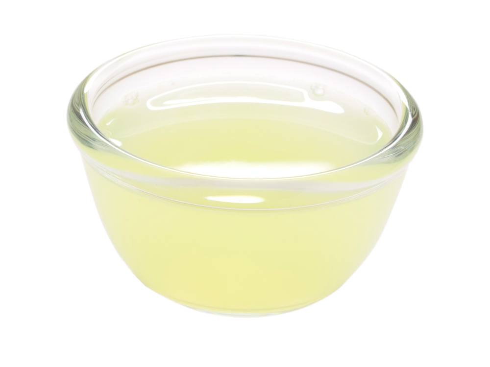 Close up of a bowl of lemon juice on white background.
