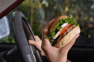 Eating hamburger in car.