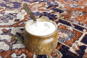 Salt in a wooden bowl with spoon over carpet.