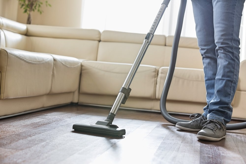 Low section of man cleaning hardwood floor with vacuum cleaner.