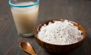 Diatomaceous in wooden bowl, a cup of diatomaceous solution and a wooden spoon on wooden table.