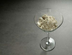 Diatomaceous earth in cocktail glass on the ground.