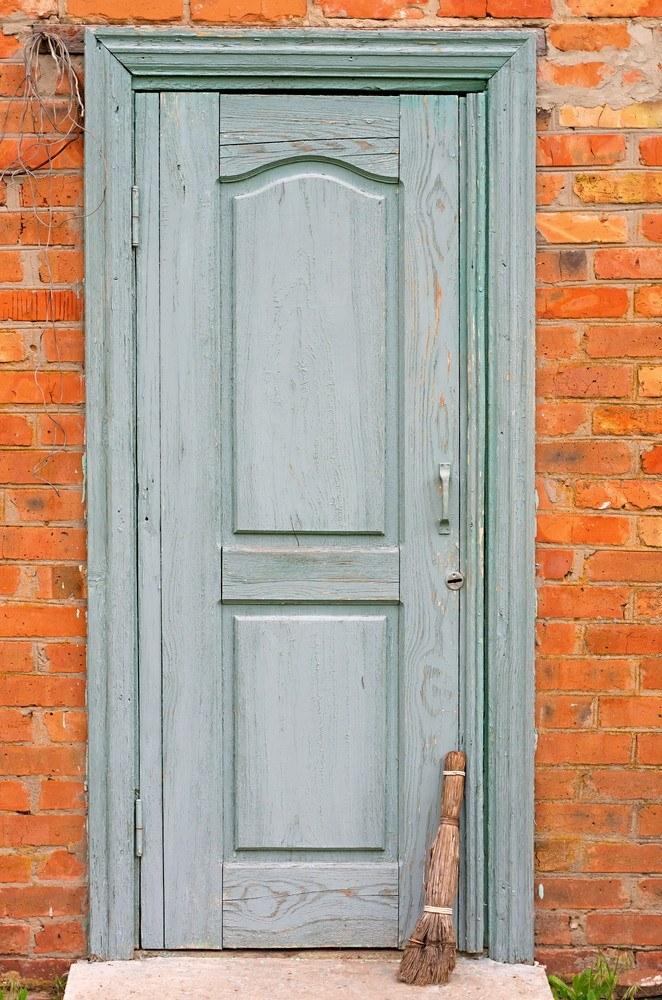 Brick wall with old wooden door, alongside worn broom.