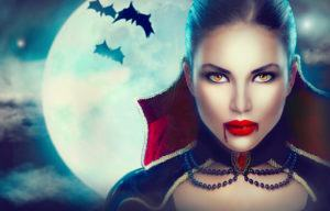 Vampire Woman portrait over scary night background with bats. Beauty Sexy Vampire Girl with dripping blood on her mouth. Vampire makeup Fashion Art design.