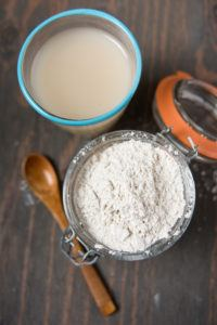 Diatomaceous earth in glass bowl with a wooden spoon aside and a cup of diatomaceous earth water nearby on wooden ground.