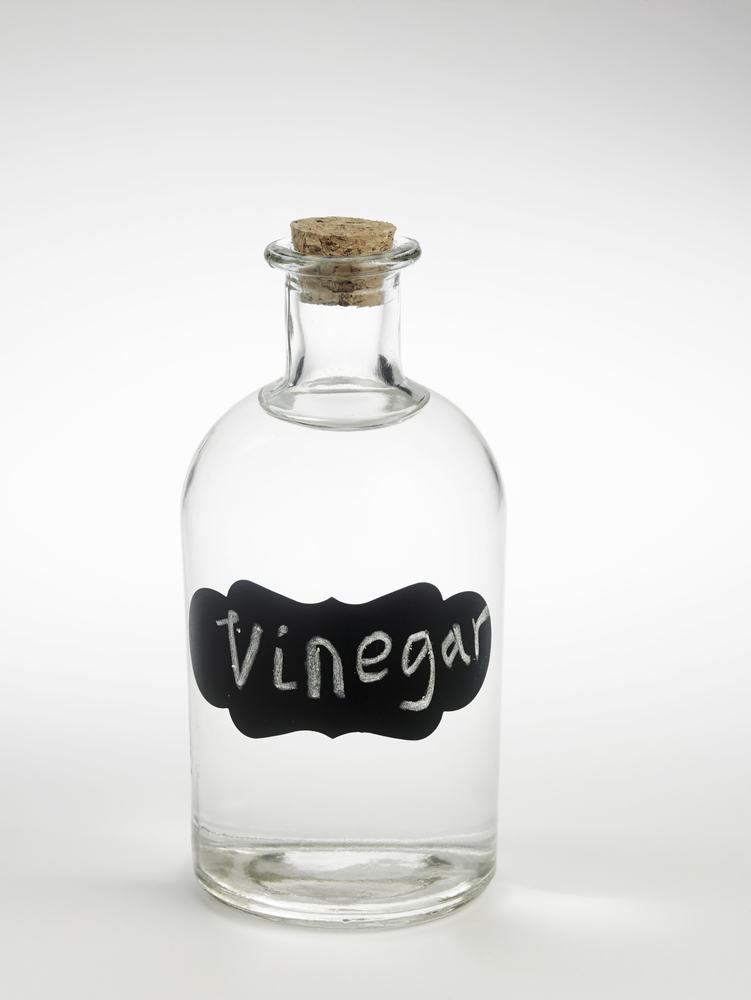 A glass bottle of colorless vinegar with black tag on white backiground.