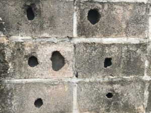 Several holes in the concrete wall.