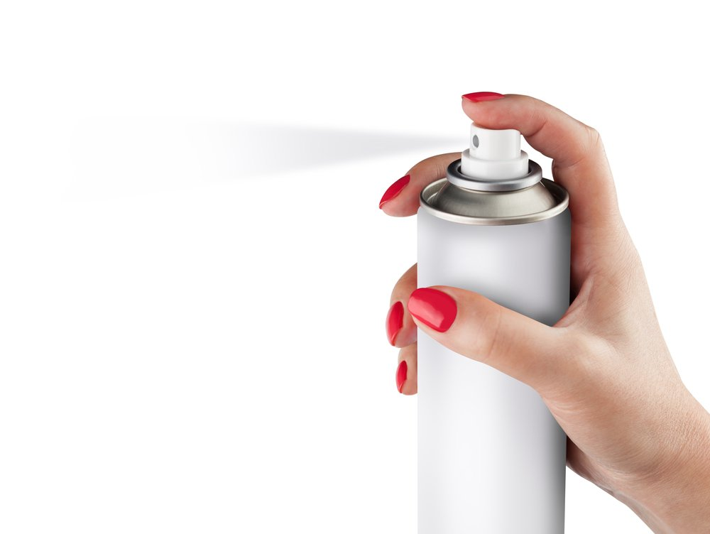 White spray can isolated on white background on a woman hand.