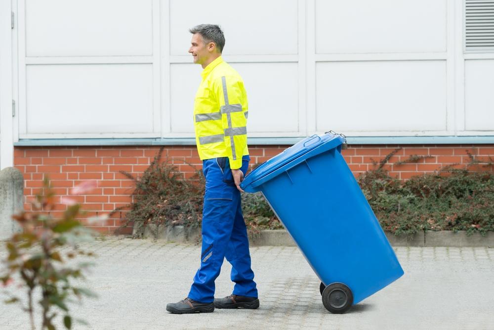 Happy male worker walking with dustbin on street.