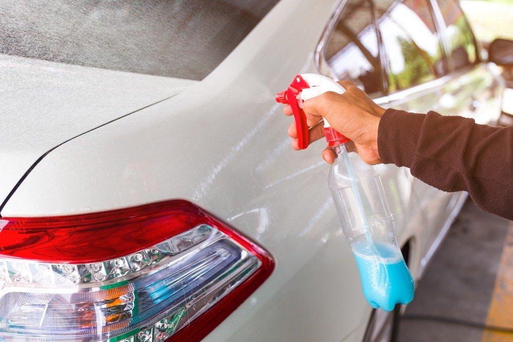 A hand cleaning car with foggy spray.