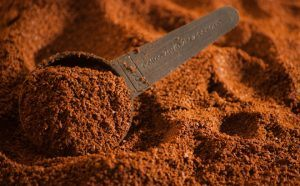 Coffee grounds with a spoon.