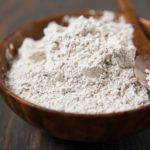 Diatomaceous in wooden bowl with wooden spoon on wooden table.
