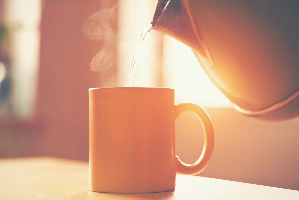 Kettle pouring boiling water into a cup in morning sunlight.