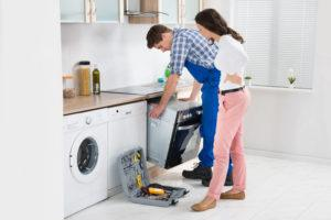 Young woman looking at male worker in overall repairing oven in kitchen.