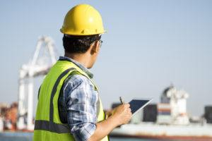A male engineer is inspecting container in port.