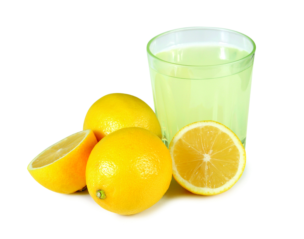 Lemon juice and lemons on the white.