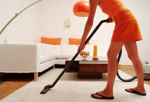 Woman is vacuuming the house.