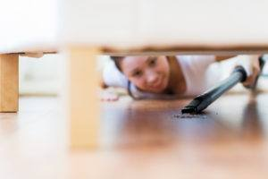 Close up of happy woman with vacuum cleaner cleaning floor under couch at home.