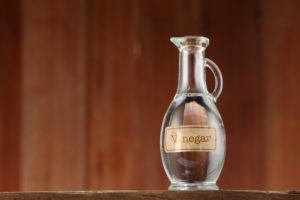 White vinegar on wooden background.