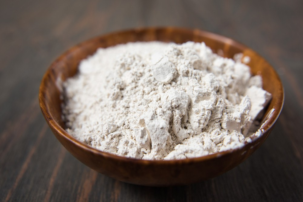 Diatomaceous Earth in wood bowl on wooden ground.