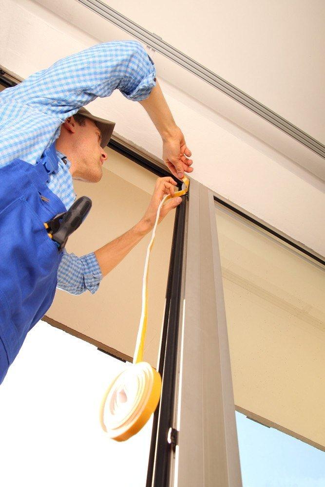 Professional sealing a window frame.